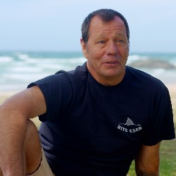 shark attack survivor Dave Pearson, talks to camera while sitting with the ocean behind him